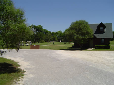 A photo of the cabin area with some people playing golf in the background.