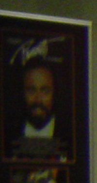 A blown up photo of Pavarotti that was taken in the background of a photo of Laura an me